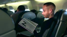 华沙,波兰- 2016年12月, 24日 听到音乐和读在飞机客舱的年轻人杂志 库存照片
