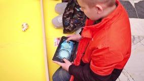 华沙,波兰- 2017年3月, 4日 操作小电罗经机器人Sphero的男孩使用片剂个人计算机 4k射击 免版税库存图片