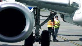 华沙,波兰- 2017年5月, 18日 机场人员被检查的波音737商业班机 远摄镜头 库存图片