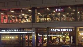 华沙,波兰- 2016年12月, 22日 跑在踏车的人们在城市健身房和现代咖啡馆店面在晚上 图库摄影