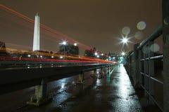 华盛顿纪念碑升在晚上在雨中与从汽车的光足迹 库存图片