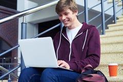 华美男性聊天在膝上型计算机,当坐台阶时 免版税库存照片
