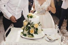 华美的一起削减白色婚礼的新娘和时髦的新郎 免版税库存图片