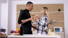 华美的人种间在厨房的夫妇饮用的酒 股票视频