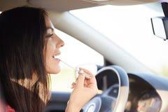 华美的典雅的年轻女性在汽车使用镜子到在嘴唇,她的秀丽关心的appy唇膏,有时间为组成,当是s时 免版税库存图片