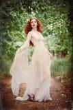 华美的在森林难看的东西纹理作用的红头发人妇女佩带的白色礼服 库存图片
