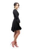 华美的女性时装模特儿侧视图在微笑对照相机摆在的黑礼服的 库存图片