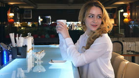 年轻华美的女性饮用的咖啡和周道看在咖啡店窗口外面,当享受她的休闲时 免版税库存图片