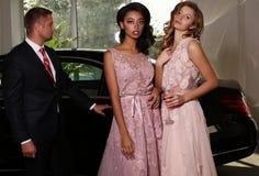 华美的女服豪华礼服,摆在黑汽车旁边 免版税库存照片