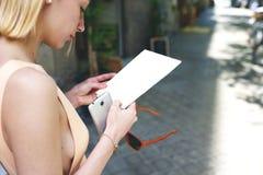 年轻华美的妇女读了空的飞行物,当站立在城市布局时 库存照片