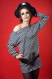 华美的妇女画象有诱惑构成佩带的海盗服装和竖起的帽子的 一把枪和匕首在她的传送带 库存照片