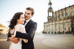 华美的婚礼夫妇在有建筑学的老镇享受一个晴天 库存照片