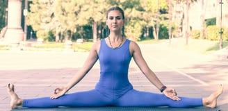 华美的室外年轻女人实践的瑜伽 平静和放松,女性幸福概念弄脏了背景 图库摄影