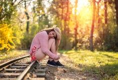 华美的少妇坐铁路 库存照片
