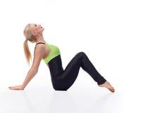 华美的少妇实践的瑜伽坐地板 库存图片