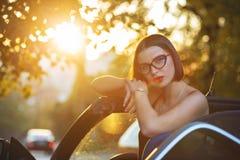 华美的式样戴着眼镜,坐在有平衡阳光的金子的一辆敞篷车汽车 文本的空间 免版税库存照片