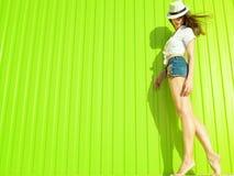 华美的微小的长腿的模型画象与长的挥动的头发佩带的白色巴拿马,女衬衫和时髦牛仔裤短裤的 免版税库存图片