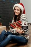 华美的微笑的深色的女孩在圣诞老人帽子和舒适毛线衣hol中 免版税库存图片