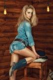 华美的性感的白肤金发的佩带的牛仔布衬衣、牛仔裤裤子和绒面革起动画象与花卉刺绣 免版税图库摄影