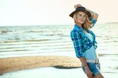 年轻华美的性感的白肤金发的模型画象在黑色的感觉头发、被检查的蓝色衬衣和站立在海边的牛仔布短裤 库存照片