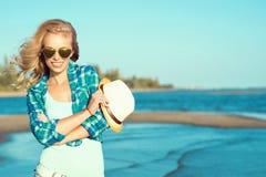 年轻华美的性感的被晒黑的白肤金发的佩带的被反映的心形的太阳镜和被检查的蓝色衬衣画象在海边 库存图片