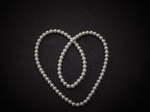 华美的惊人的白色珍珠时兴的首饰,项链塑造了当在深灰背景的华伦泰心脏 免版税图库摄影
