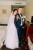 华美的摆在旅馆客房的新娘和典雅的新郎在婚礼以后 新婚佳偶画象蜜月的 图库摄影