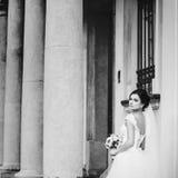 华美的新娘摆在老大厦的柱子之间 免版税库存图片