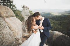华美的新娘,亲吻和拥抱在峭壁附近的新郎有惊人的看法 库存照片
