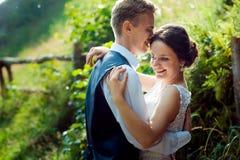 华美的新婚佳偶加上的情感画象体贴拥抱在晴朗的绿色庭院里的可爱的微笑 库存照片