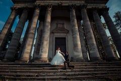 华美的新婚佳偶的室外结婚照 英俊的新郎握迷人的新娘的手,当时 免版税图库摄影
