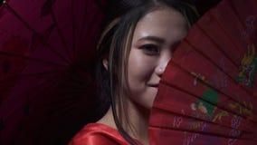 华美的日本夫人展开爱好者然后微笑并且报道一半她的面孔,关闭  影视素材