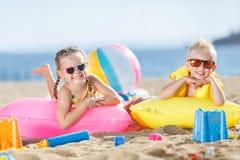 华美的晒日光浴在一个沙滩的兄弟和姐妹 免版税库存照片