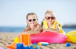 华美的晒日光浴在一个沙滩的兄弟和姐妹 免版税库存图片