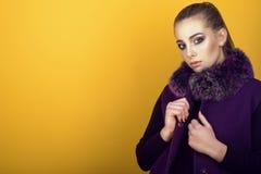 年轻华美的模型画象与穿有毛皮衣领的马尾辫和艺术性的构成的时髦紫色无袖的外套 库存图片