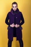 年轻华美的模型画象与穿黑皮革裤子和时髦紫色无袖的外套的马尾辫和艺术性的构成的 免版税图库摄影