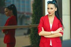 年轻华美的深色头发的女实业家和有太阳镜的金黄手表画象经典红色衣服的在她的头 库存照片