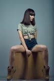 年轻华美的深色头发的模型佩带的上流画象waisted深蓝牛仔裤短裤、卡其色的衬衣和起动坐立方体 图库摄影