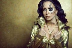 华美的深色头发的模型画象与艺术性的创造性的时钟的做佩带的套豪华金黄首饰 免版税库存照片