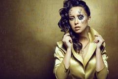 华美的深色头发的模型画象与艺术性的创造性的时钟的做佩带的套豪华金黄首饰 免版税图库摄影