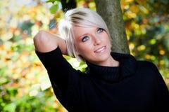 华美的白肤金发的妇女在秋天 免版税库存照片