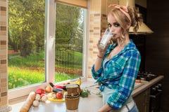 华美的白肤金发的主妇饮用奶画象在厨房里 水果和蔬菜在桌上 库存图片
