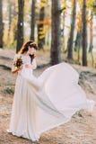 华美的白色礼服的美丽的无辜的年轻深色的新娘在森林 库存图片