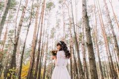 华美的白色礼服的美丽的无辜的年轻深色的新娘有在松木森林的花束的 免版税库存图片
