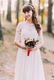 华美的白色礼服的美丽的无辜的年轻深色的新娘有花花束的在森林的 库存图片
