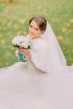 华美的白色礼服的迷人的新娘有长的面纱的坐拿着婚礼花束的草 图库摄影