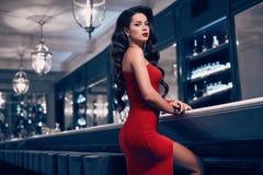 华美的红色礼服的秀丽年轻深色的妇女 库存照片