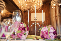 华美的花的布置在婚礼桌上 并且三个蜡烛的烛台在枝形吊灯背景  免版税库存照片