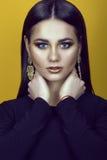 年轻华美的蓝眼睛的深色头发的模型画象与专家的在戴着黑上面和耳环的金黄颜色组成 库存图片