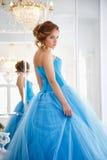 华美的蓝色礼服灰姑娘样式的美丽的新娘在镜子附近 免版税库存照片